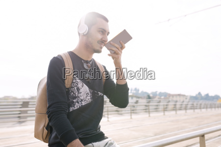 young man with headphones and cell
