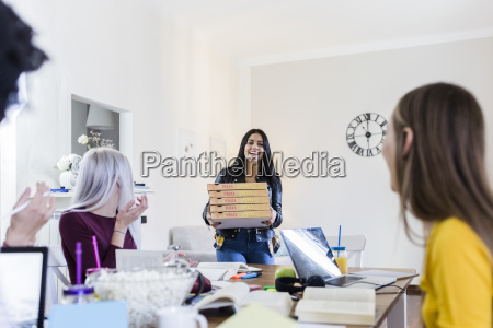 young women bringing pizza for friends