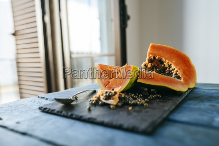 papaya cut on slate on blue