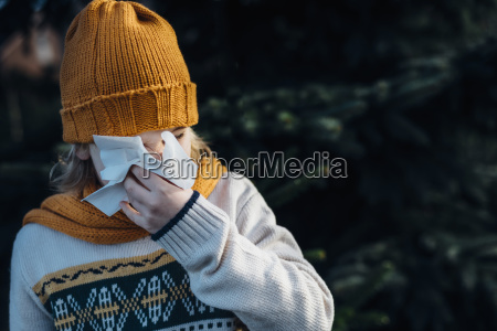 little boy having a cold blowing