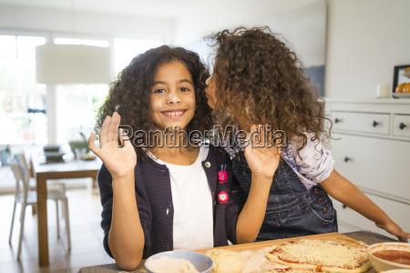 little girl kissing sister in kitchen
