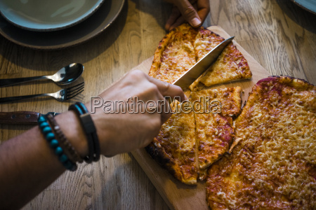 hand cutting crispy homemade pizza with