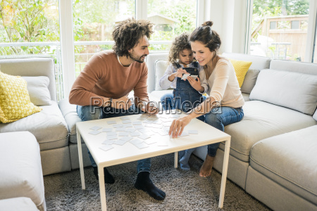family sitting on couch playing