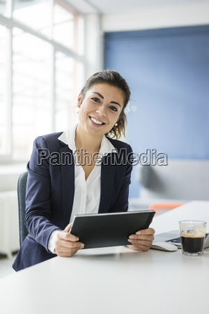 portrait of happy businesswoman with tablet