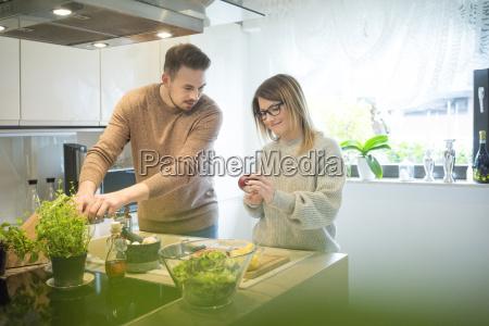 couple preparing salad in kitchen together