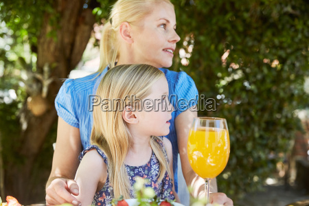 girl with mother sitting at garden