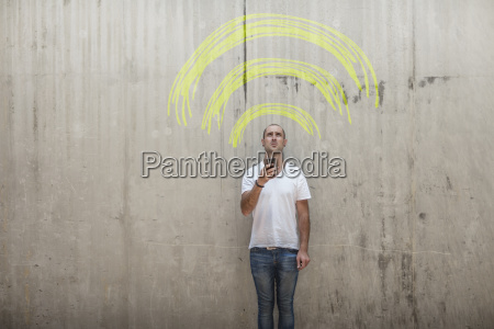 man holding cell phone with yellow