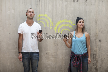 man and woman holding their phones
