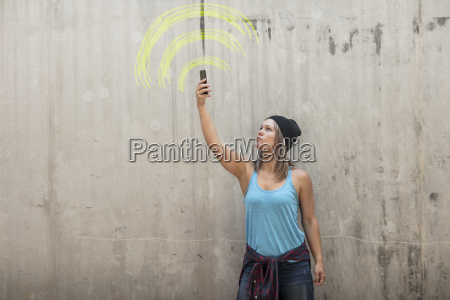 woman holding up phone looking for