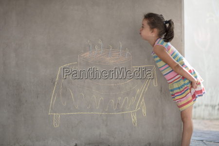 girl pretending to blow out chalk