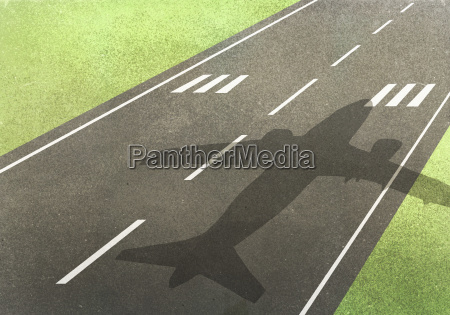 shadow of airplane on runway amidst