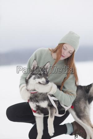beautiful young woman stroking siberian husky