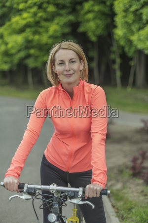 portrait of smiling woman with bicycle