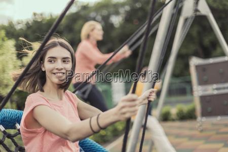 smiling women swinging on swing at