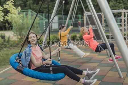 full length of happy women swinging