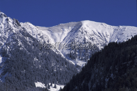 avalanche control in snowy mountain landscape