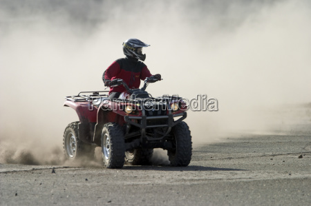 quad drives on a dusty track