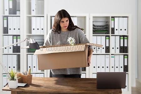 businesswoman carrying her belongings in office