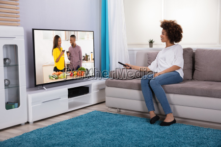 young woman holding remote watching television