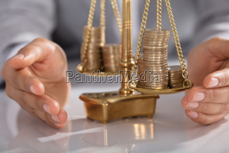 businessperson protecting justice scale with stacked