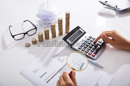 businessperson analyzing bills with magnifying glass