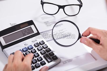 businessman hand examining invoice