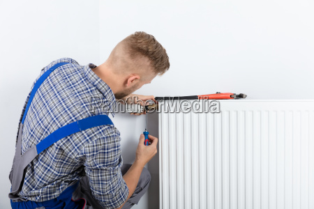 male plumber fixing thermostat