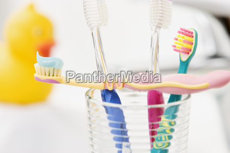 four colorful toothbrushes in a glass