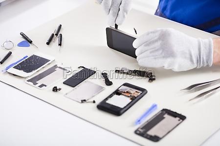 human hand repairing smartphone