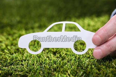 person holding paper car on grass