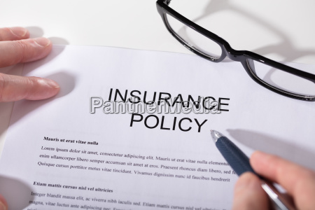 persons hand over insurance policy form
