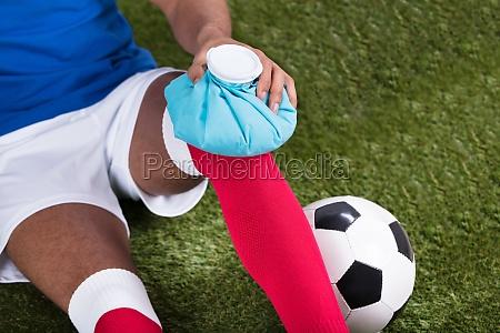 ferito calcio giocatore applicando ice pack