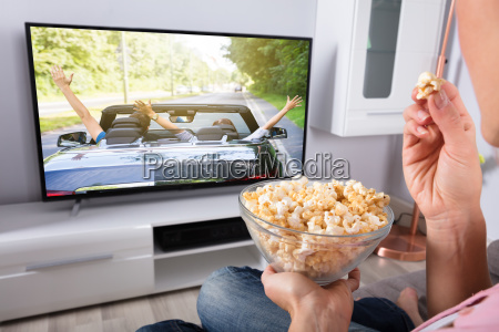 persons hand holding popcorn while movie