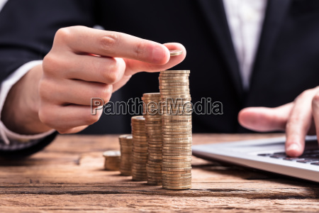 businessperson placing a coin on increasing