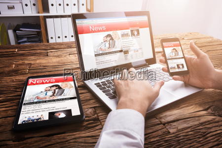 businessperson reading online news on laptop