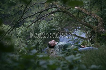 caucasian man relaxing in woods