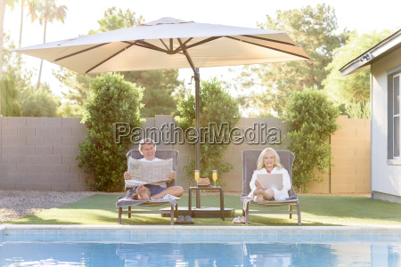 caucasian couple reading newspaper and using