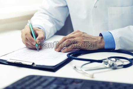 doctor working in office writing documents