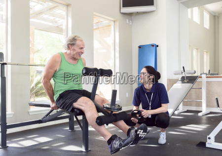 caucasian trainer watching man strengthen legs