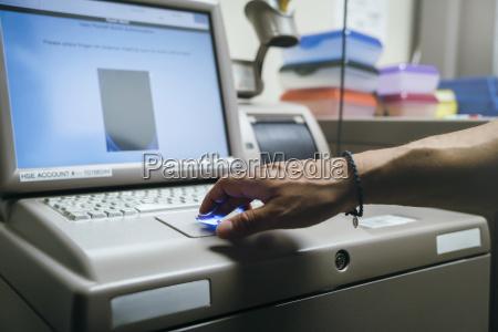 mixed race nurses using fingerprint scanner