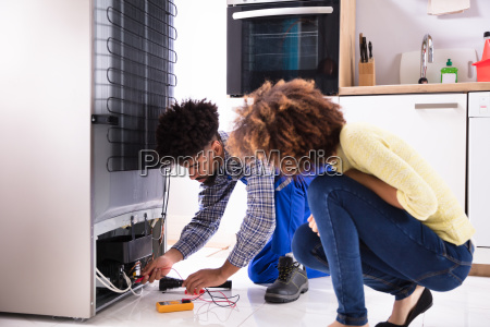 technician examining refrigerator with digital multimeter