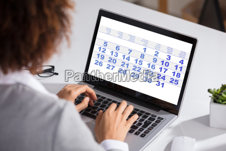 businesswoman looking at calendar with daily