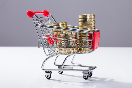 shopping cart filled with stacked coins