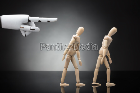 robots hand giving direction to two