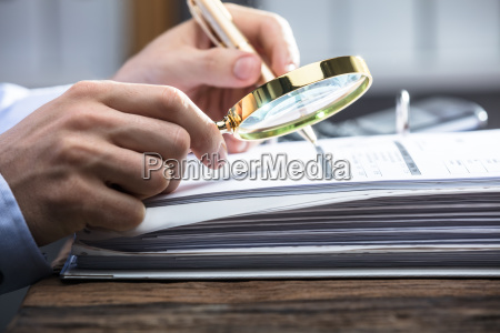 businessperson looking at invoice through magnifying