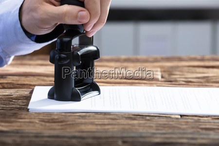 businessperson stamping with approved stamp on