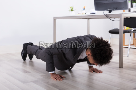 businessman doing push up in office