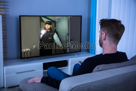 man watching suspense movie on television