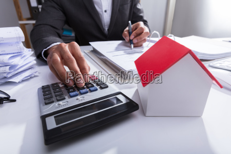 businessperson calculating bill in office
