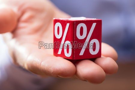 hand holding red block with percentage